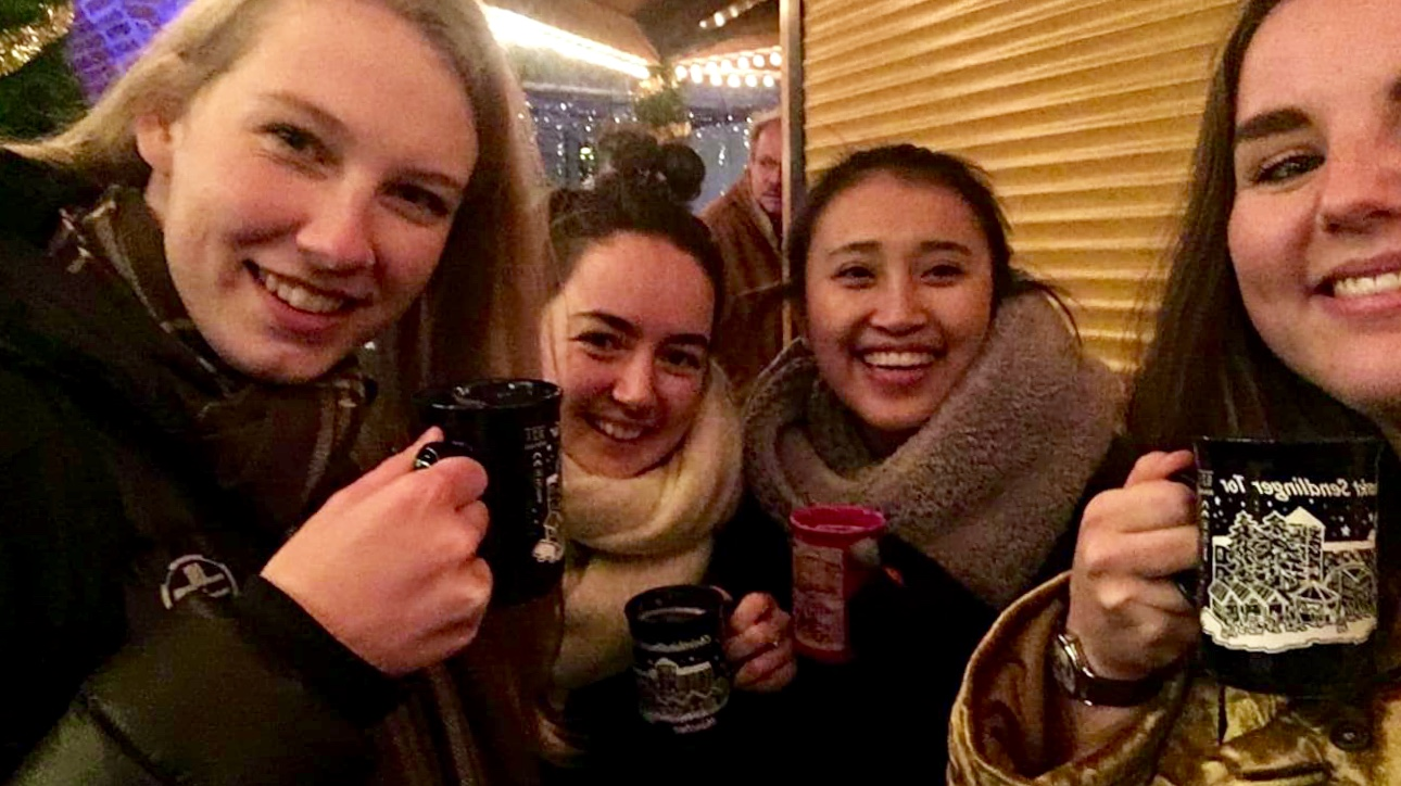 Jasmine and her friends at the Sendlinger Tor Christmas market holding warm mugs.