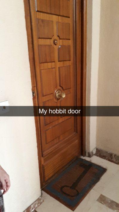 """A wooden door with a Snapchat caption describing it as a """"hobbit door"""""""
