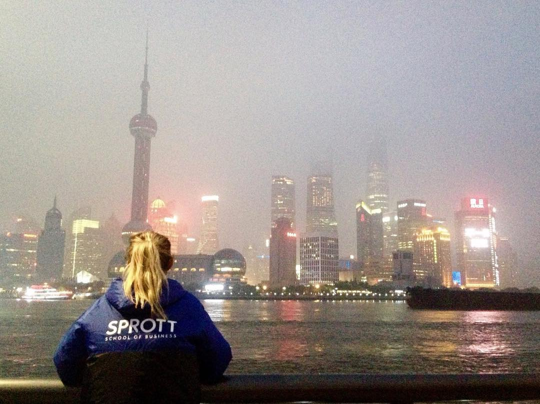 Sophia in a Sprott sweater looking out at the Shanghai skyline