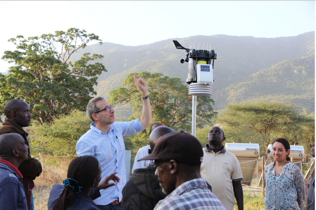 Troy Anderson with a group of people in Tanzania. He is pointing upwards at a machine as the others listen.