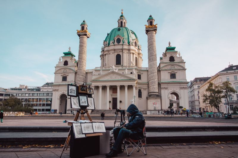 Picture of the Karlskirche church, with an artist on the street in front of it