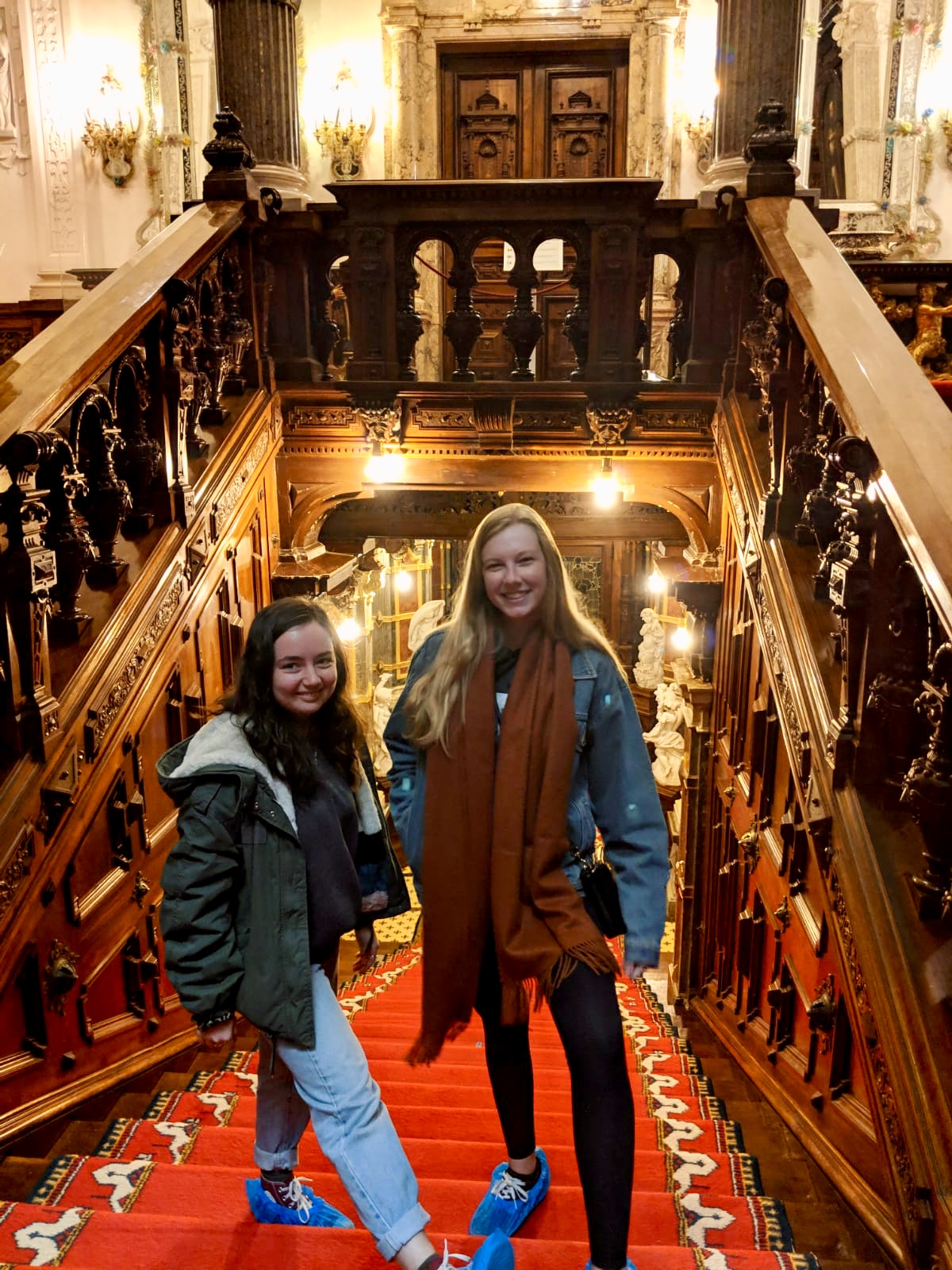 Jasmine and her friend wearing blue shoe covers inside the very ornate castle.