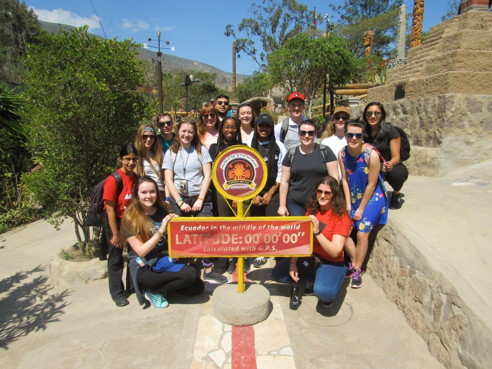 "Kiana and her group members gathered around a sign that reads ""Ecuador in the middle of the world""."