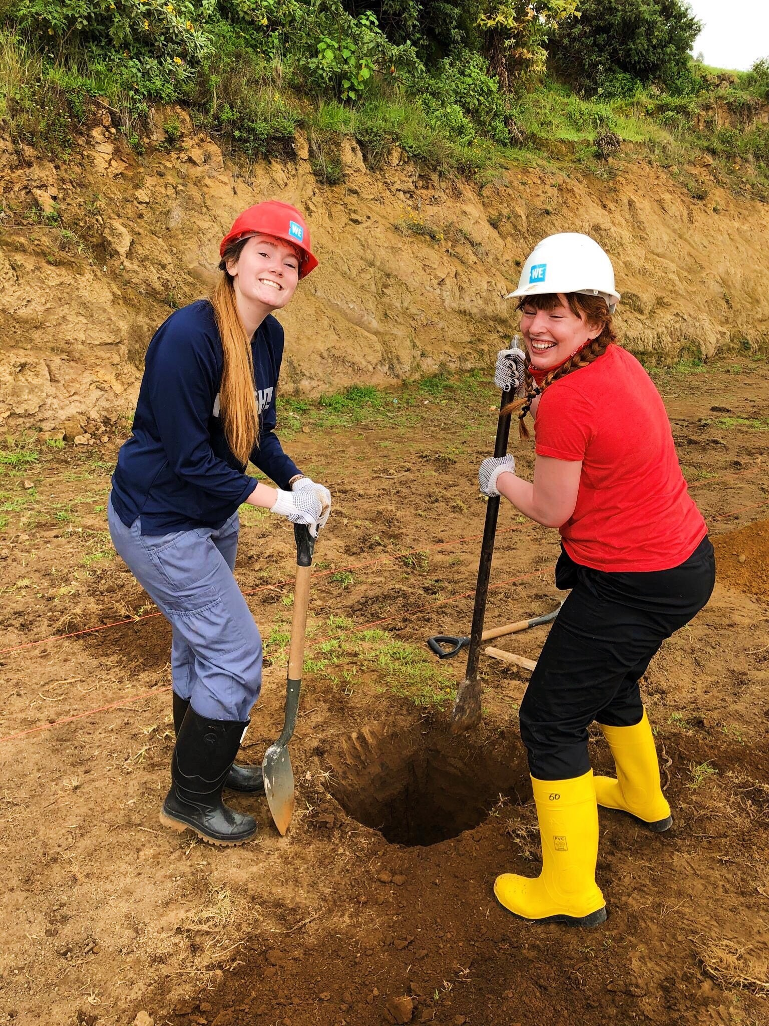 Kiana (right) pictured with group members digging a hole in the ground to be used as the foundation of a greenhouse.