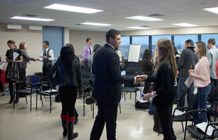 Students walking around a classroom practicing their networking skills, with a focus on two students to the right shaking hands.