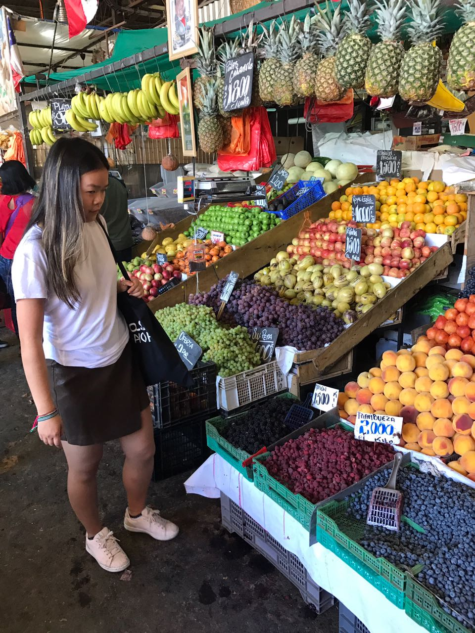 Alex looking at fresh fruit in the market