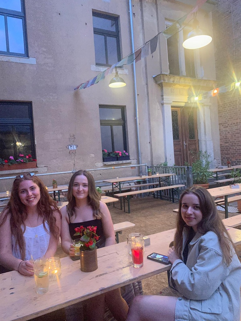 Lauren with 2 friends having drinks at an picnic table