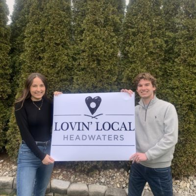 """A picture of Jake Cuthbert and Kylie MacEachern holding up a """"Lovin' Local Headwaters"""" Sign."""