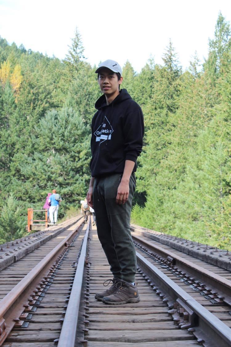 Matthew Zee standing on some old train tracks.