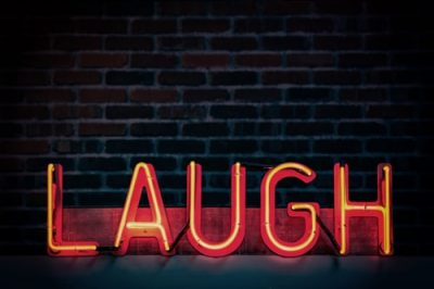 LAUGH in neon lights against a brick wall