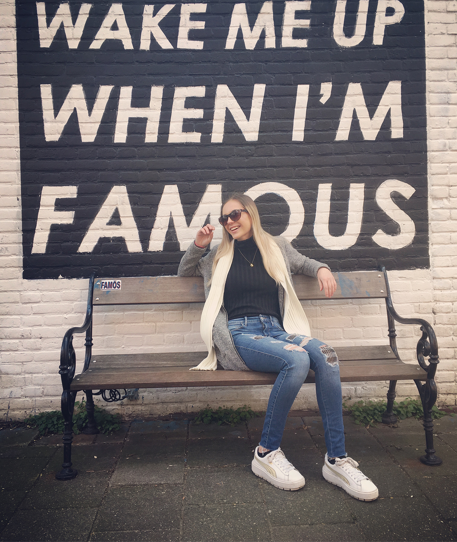 "Sarah Jane sitting on a bench in front of a sign that says ""Wake Me Up When I'm Famous"""