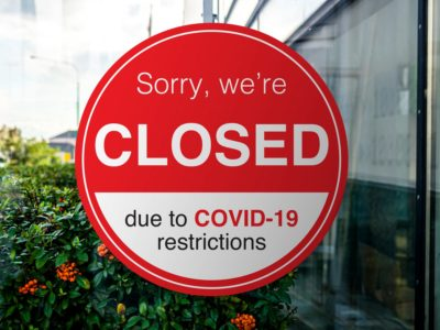 Picture of a sign on a window saying that they're closed due to COVID-19