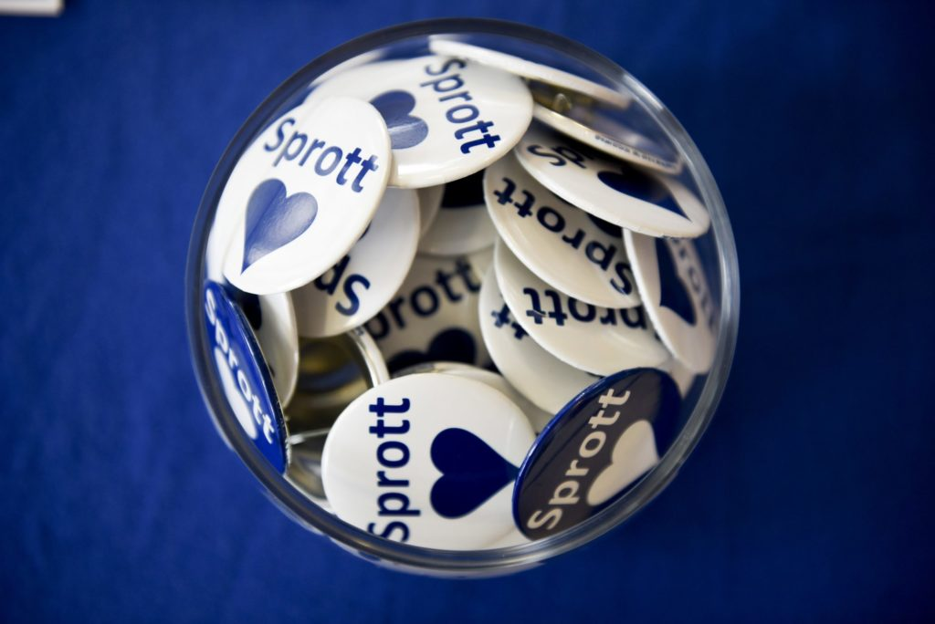 a bowl of pins that say Sprott Love