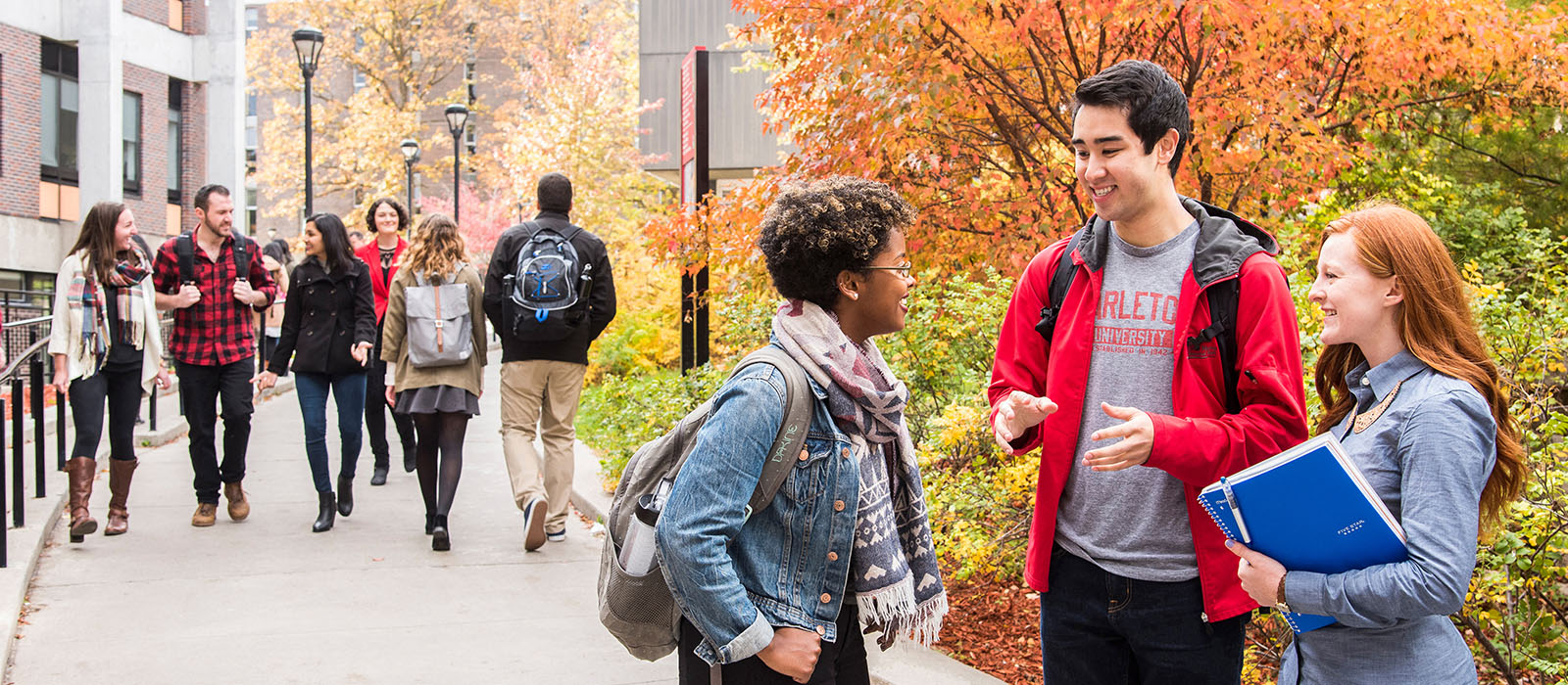 A group of students talking together on the Carleton University campus in the fall.