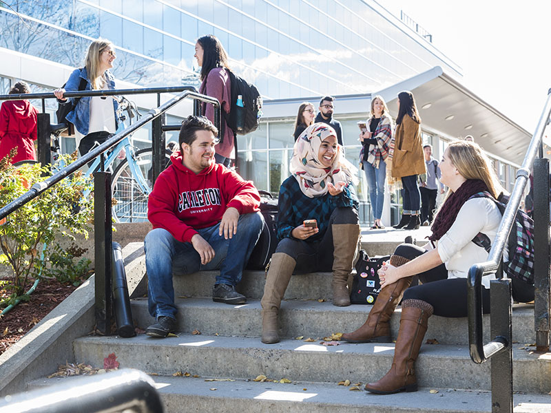 a group of students conversing while sitting outside on stairs of a walkway.