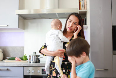 Mother talking on the phone with an upset expression, holding a baby and a small child nearby.